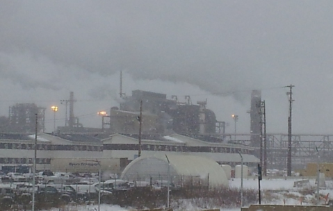 Countless smokestacks at the Syncrude plant billowed dark smoke into the overcast sky.