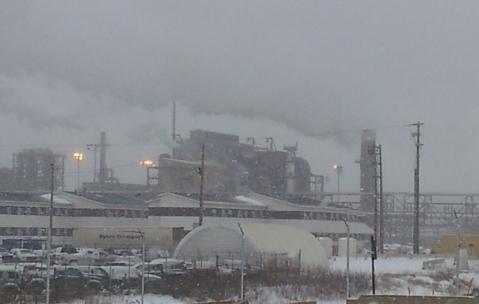 Countless smokestacks at the Syncrude plant billowed dark smoke into the overcast sky.